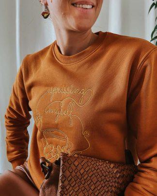woman in caramel espressing sweatshirt