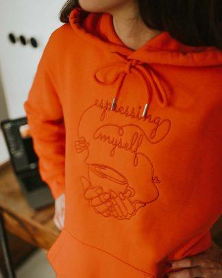 detail of espresso hoodie in tangerine