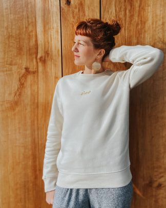 woman in cream sweatshirt with gold ciao embroidery
